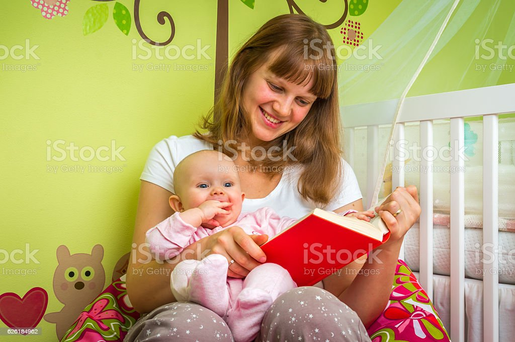 Happy mother reading a book to her baby girl stock photo