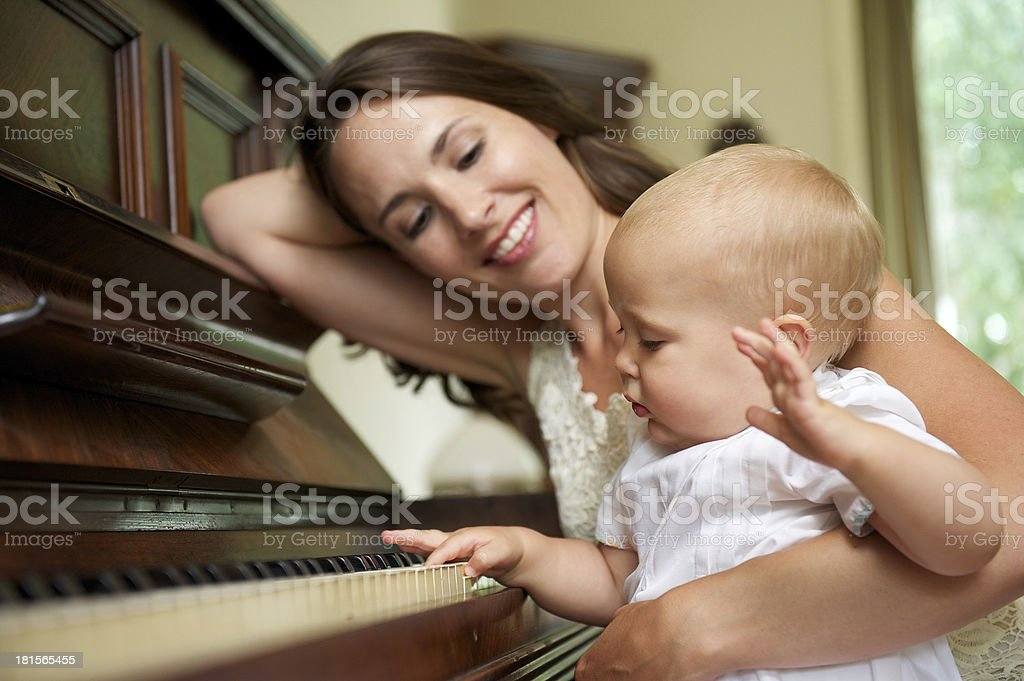 Happy mother smiling as baby plays piano royalty-free stock photo