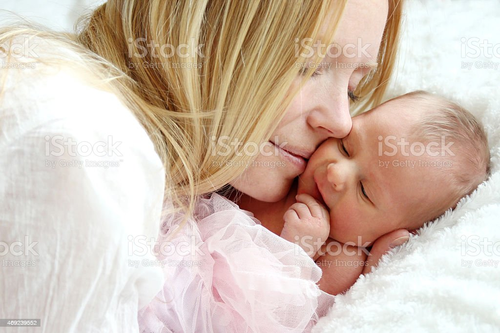 Happy Mother Snuggling Newborn Baby in Bed stock photo