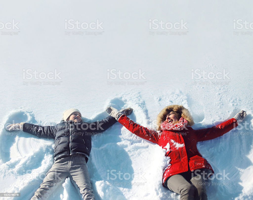 Happy mother, son playing having fun lying in snow winter stock photo