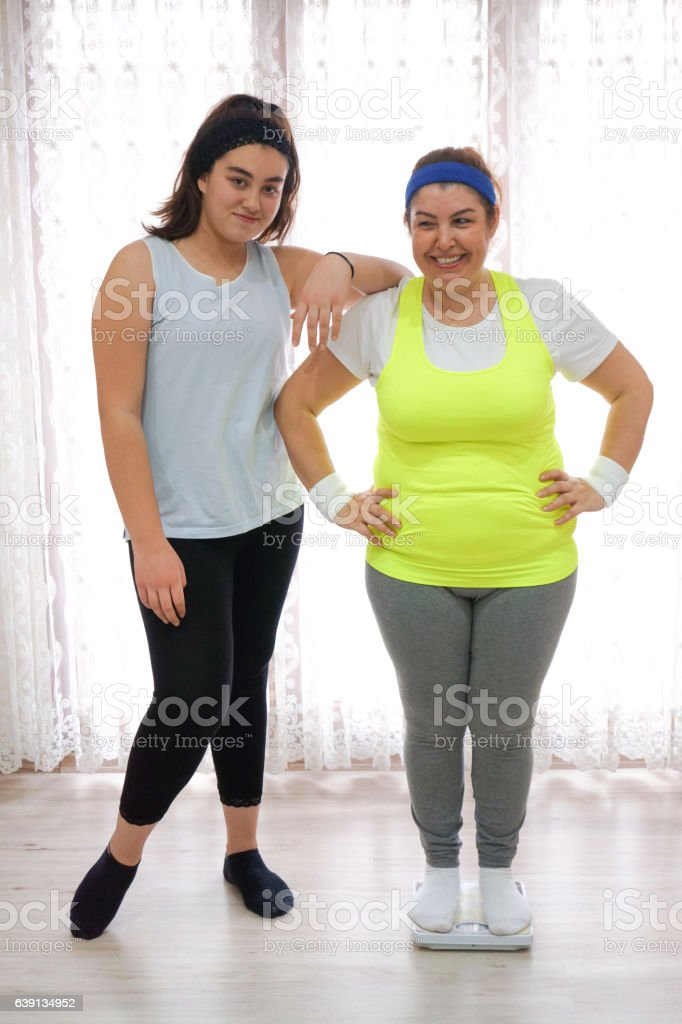 Happy mother standing on weight scale after exercise stock photo