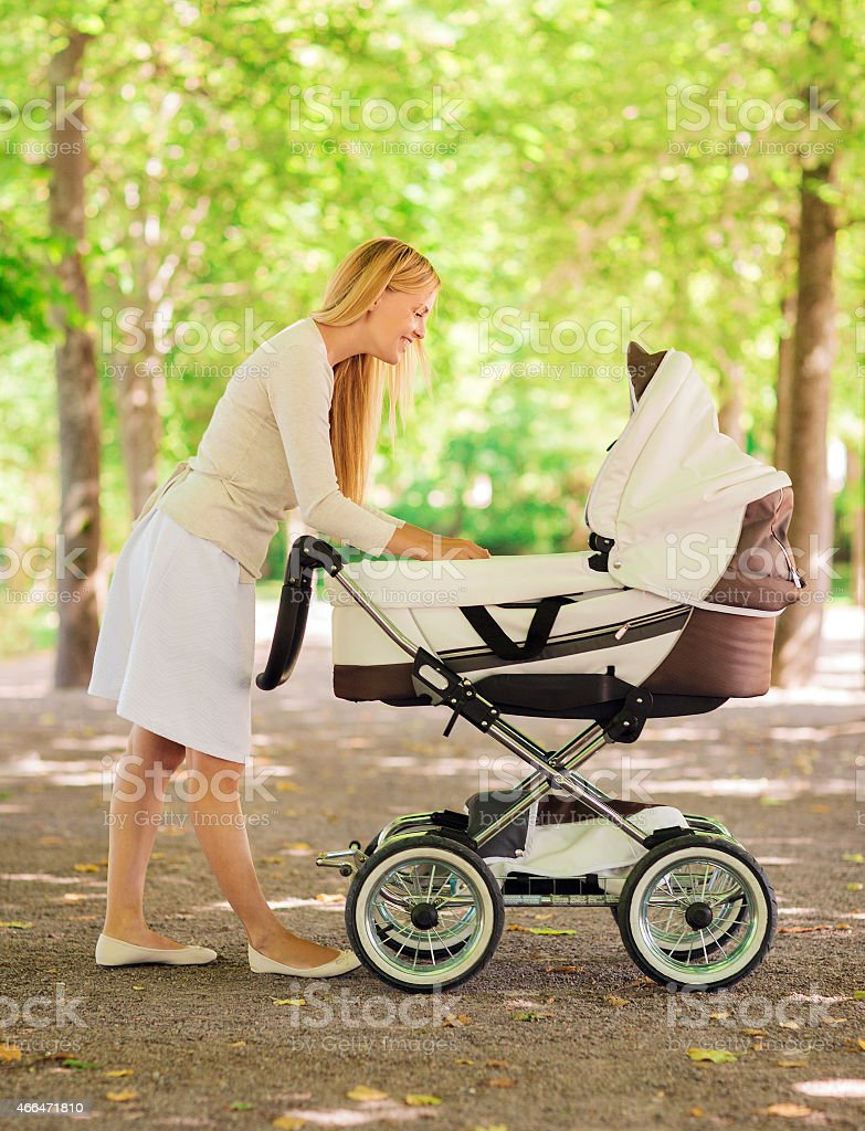 A happy mother taking her baby to the park in a stroller stock photo