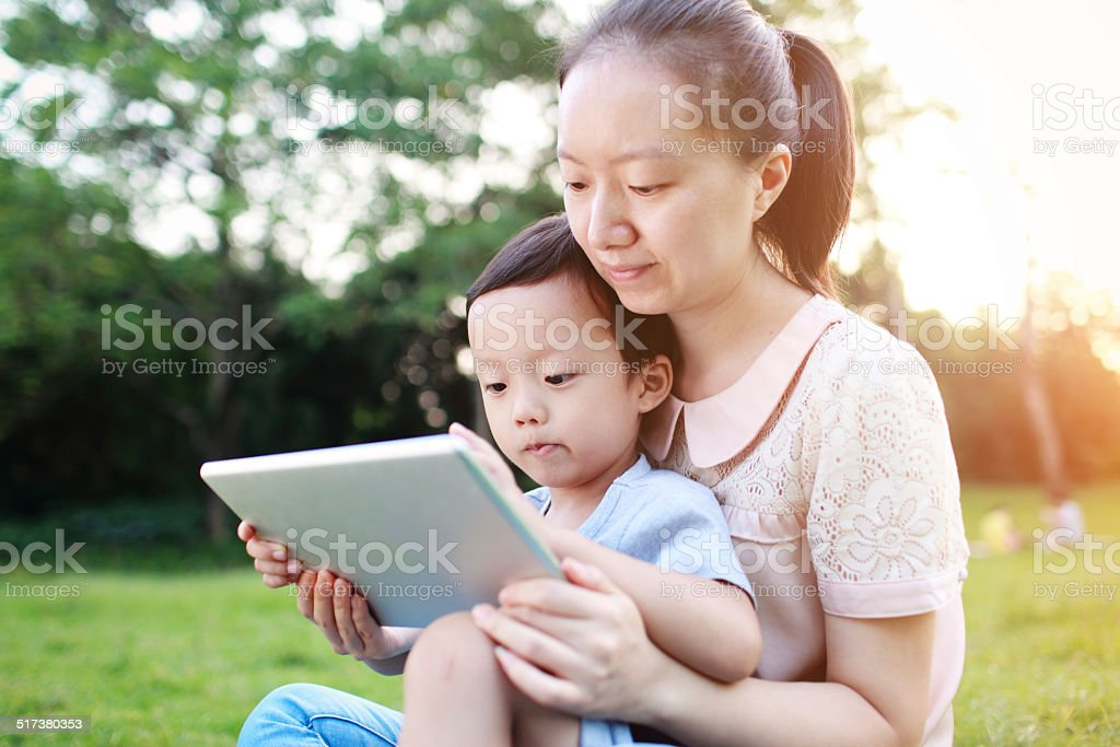 happy mother teaching little boy with tablet stock photo