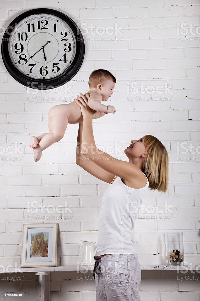 Happy Mother throws baby into the air stock photo
