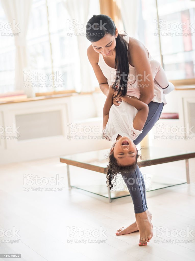 Happy mother tickling her daughter stock photo