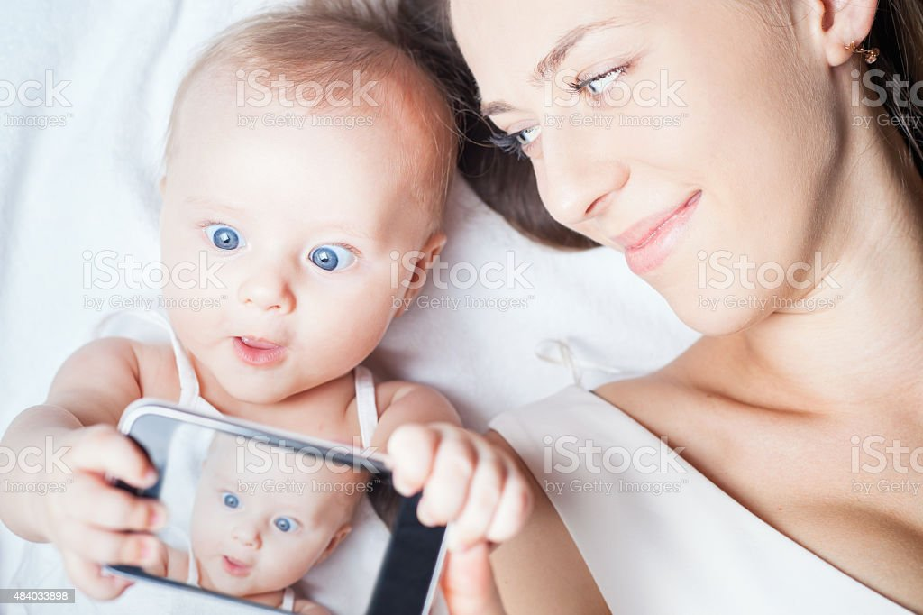 Happy mother with a baby lying on a white bed stock photo