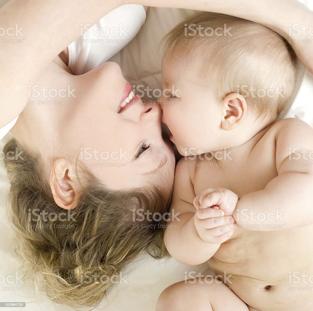 Happy mother with cute baby in bed royalty-free stock photo
