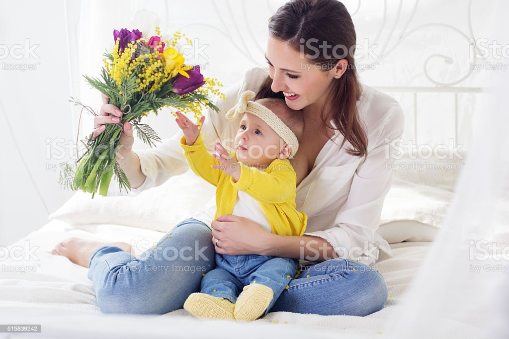 Happy mother with her baby girl and bouquet of flowers stock photo