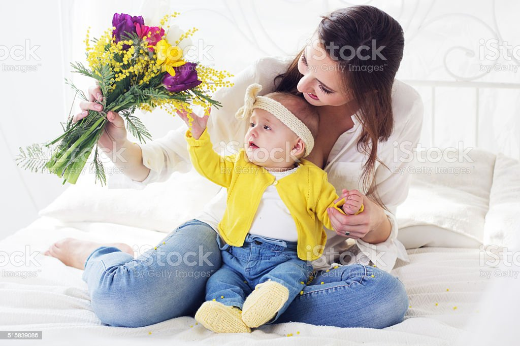 Happy mother with her baby girl in bed stock photo