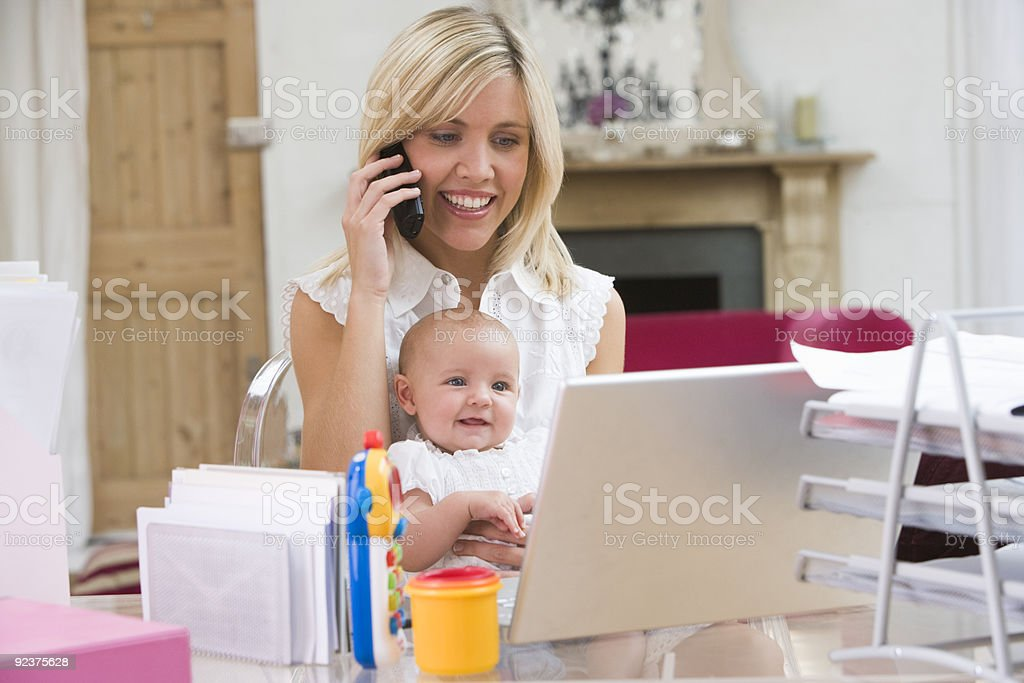 A happy mother with her baby working at a home office stock photo