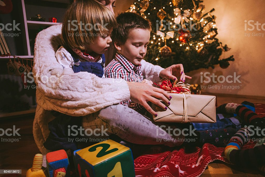 Happy Mother Wrapping Out Presents With Two Kids stock photo
