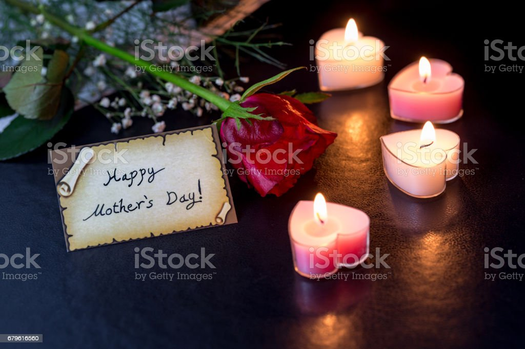 Happy mother's day card with rose and heart shaped candles in darkness stock photo