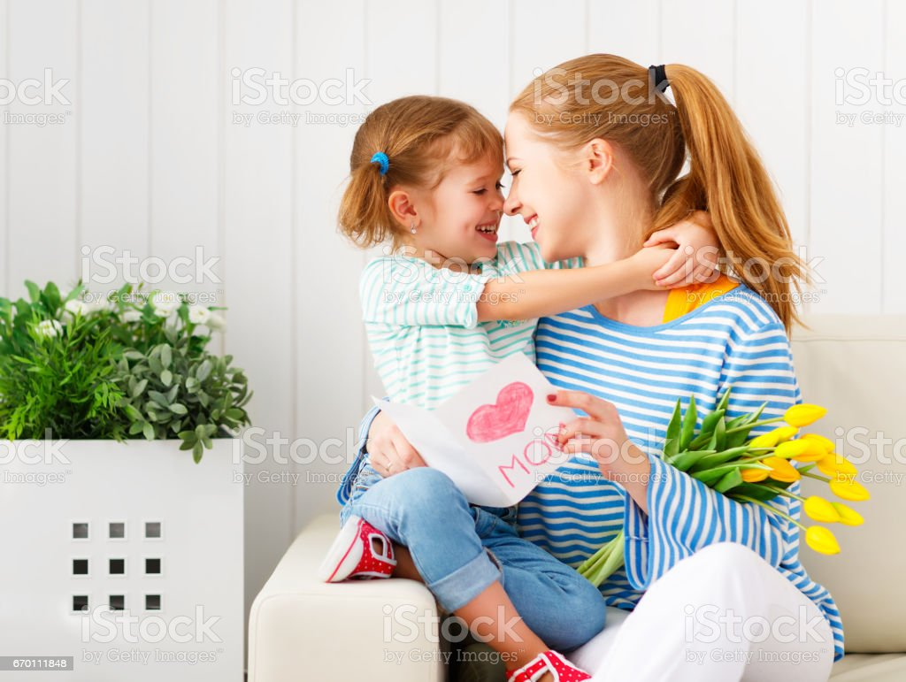 Happy mother's day! Child daughter congratulates moms and gives her a postcard and flowers stock photo