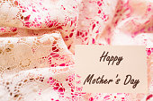 Happy Mother's Day.  White note card on lace, pink satin.