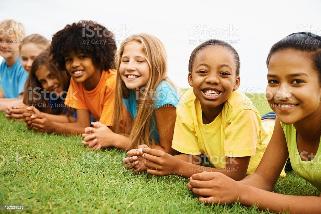 Happy multi ethnic kids lying on grass royalty-free stock photo