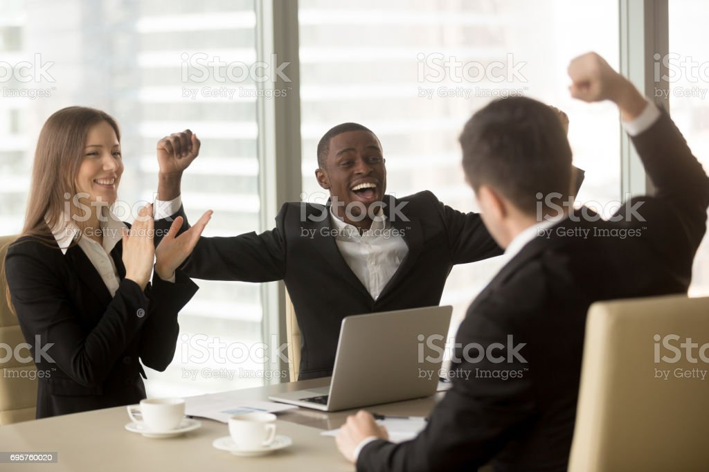 Happy multi-ethnic business team celebrating victory, raising hands and applauding stock photo