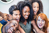 Happy multi-ethnic friends taking selfie at home