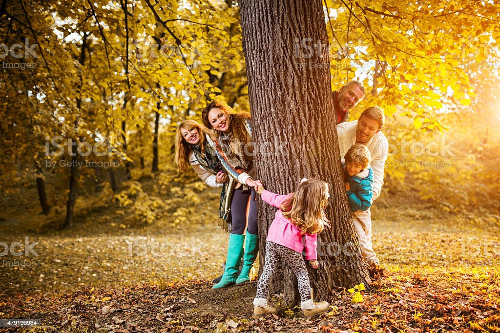 Happy multi-generation family playing around the tree in nature. stock photo