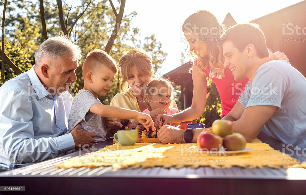 Happy multi-generation family playing chess in the garden. stock photo