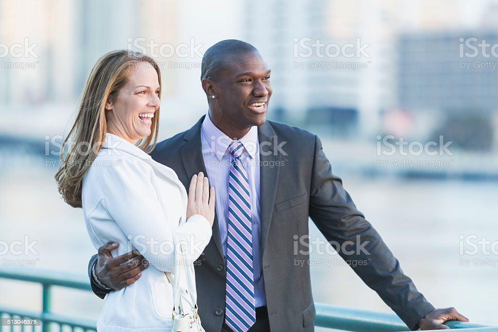 Happy multi-racial couple laughing, man wearing suit stock photo
