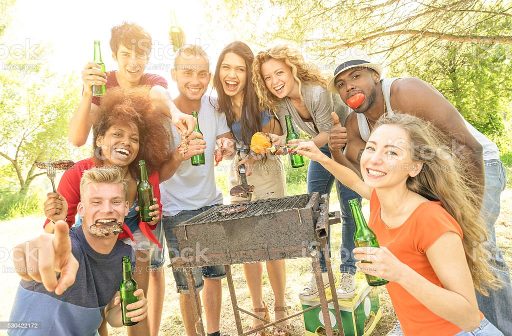 Happy multiracial friends having fun at picnic barbecue garden party stock photo