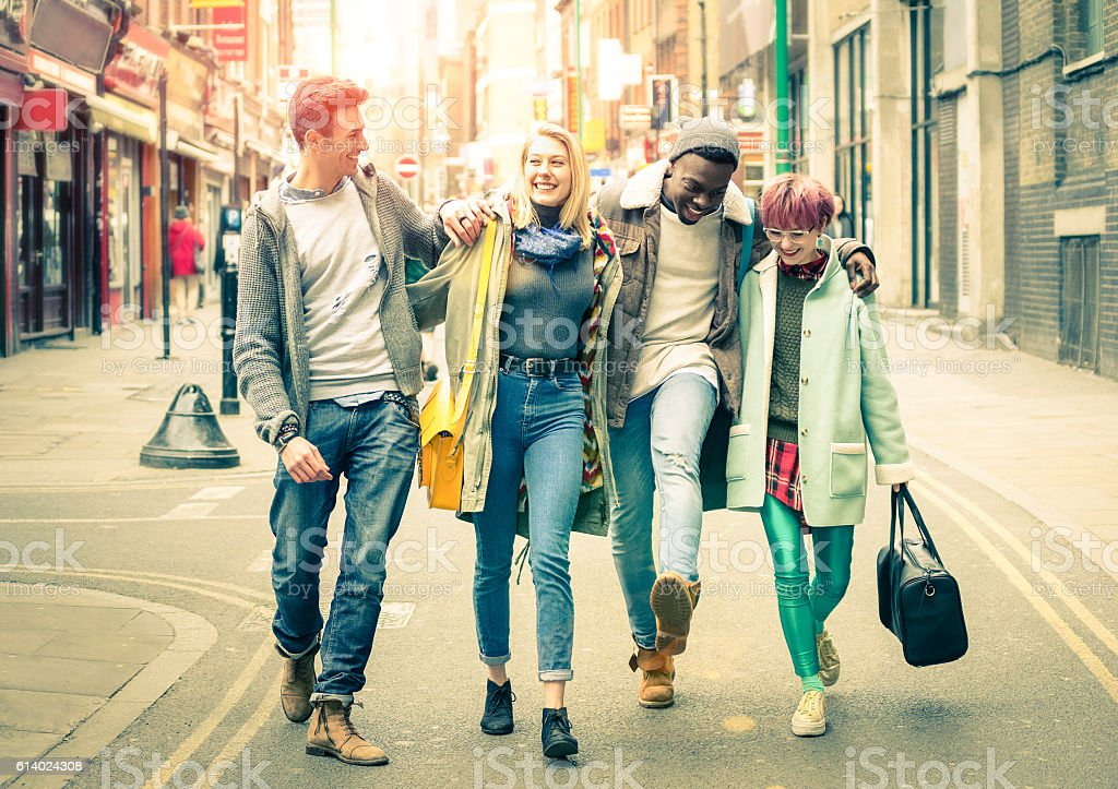 Happy multiracial friends walking on Brick Lane at Shoreditch London stock photo