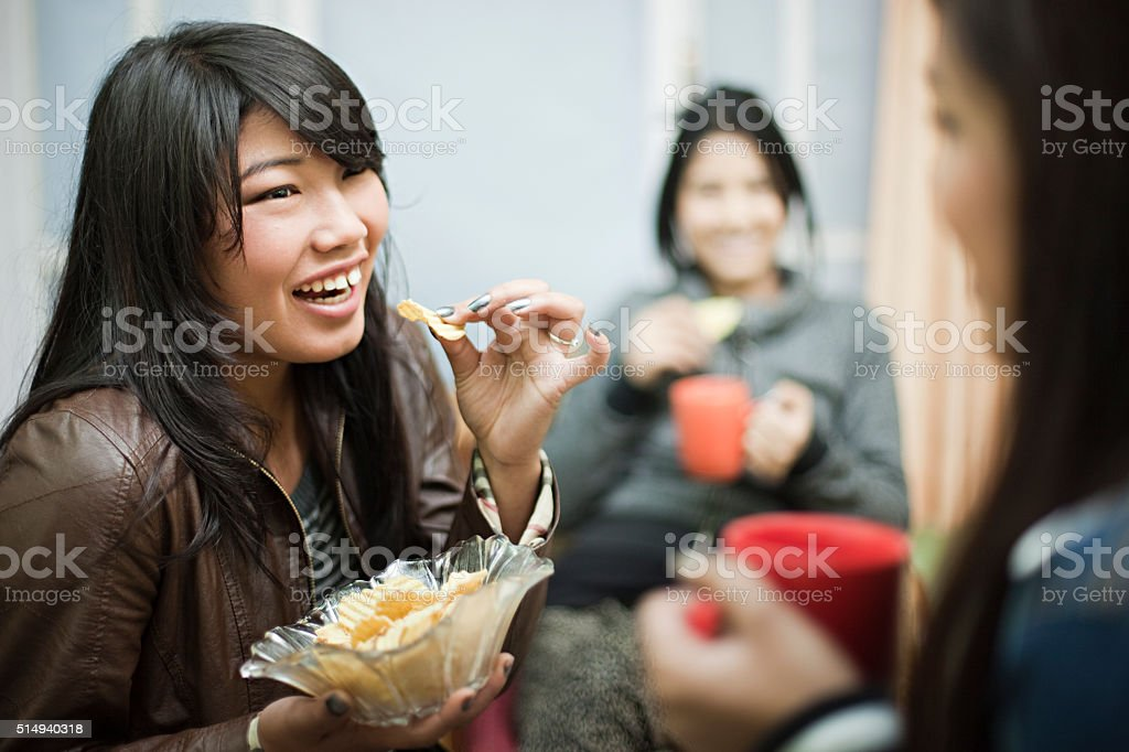 Happy multiracial group of female friends enjoying coffee with snacks. stock photo
