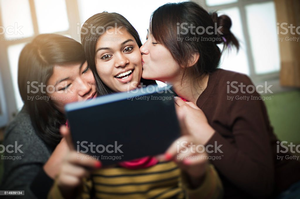 Happy multiracial group of female friends sharing digital tablet. stock photo