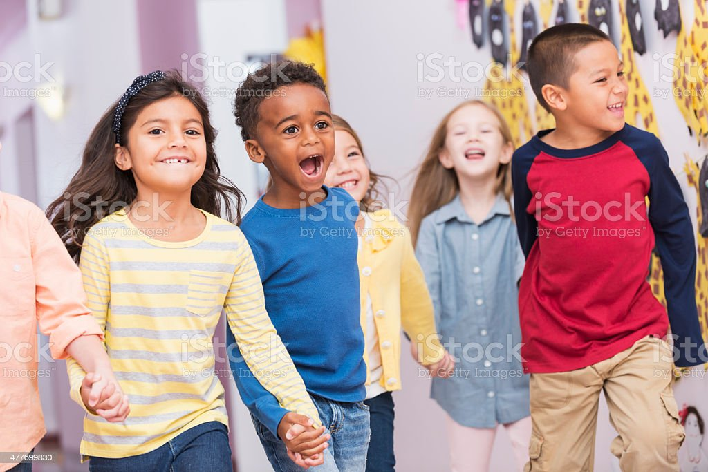 Happy multiracial school children walking thru hallway stock photo