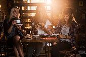 Happy multi-tasking female friends enjoying a day in a cafe.
