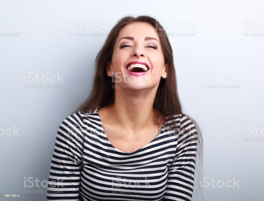 Happy natural laughing young casual woman with wide open mouth stock photo