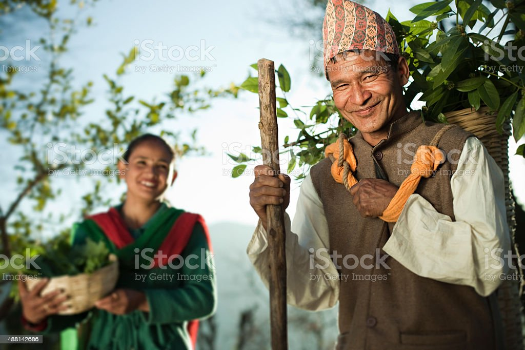 Happy Nepalese peasant with their daily needs in rural area. stock photo