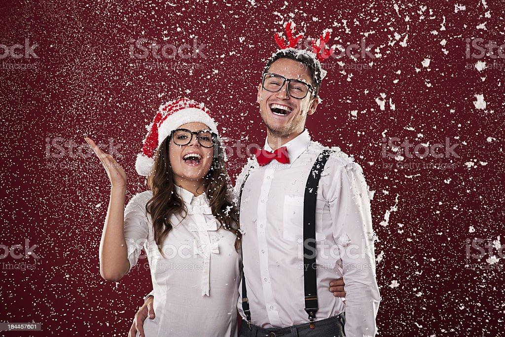 Happy nerd couple surrounded in snowflakes stock photo