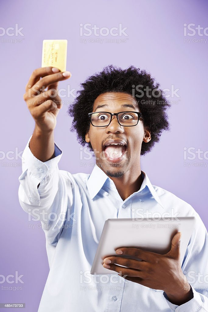 Happy nerd with digital tablet discovers E-commerce. It's a revelation! stock photo
