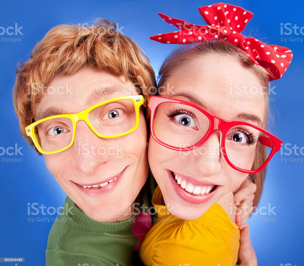 Happy nerdy couple embracing stock photo