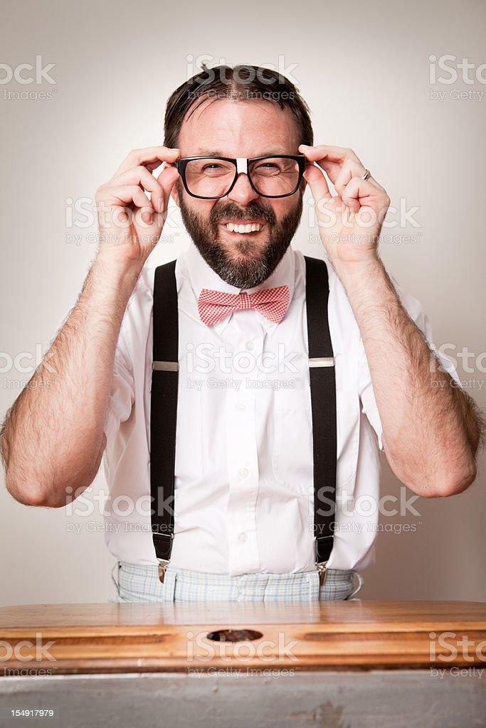 Happy, Nerdy Man Student Sitting in School Desk Adjusting Glasses stock photo