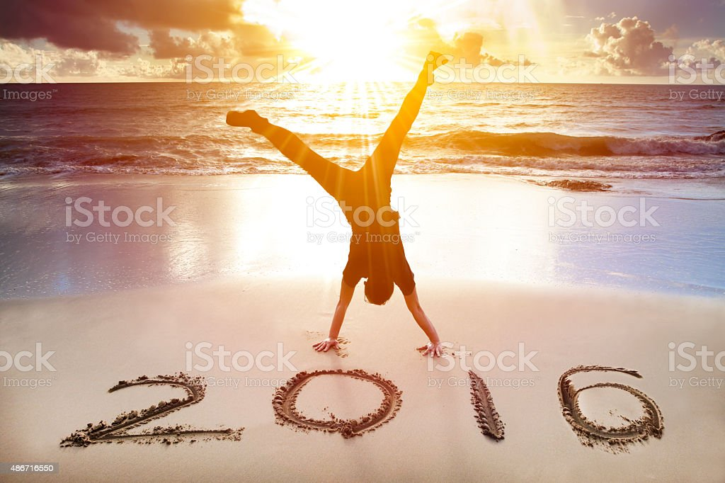 happy new year 2016. young man handstand on the beach stock photo