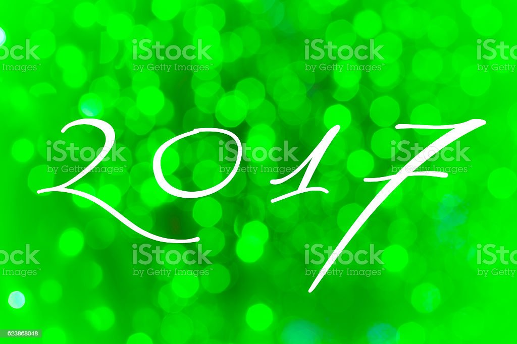Happy new year 2017 written on green tone bokeh background royalty-free stock vector art