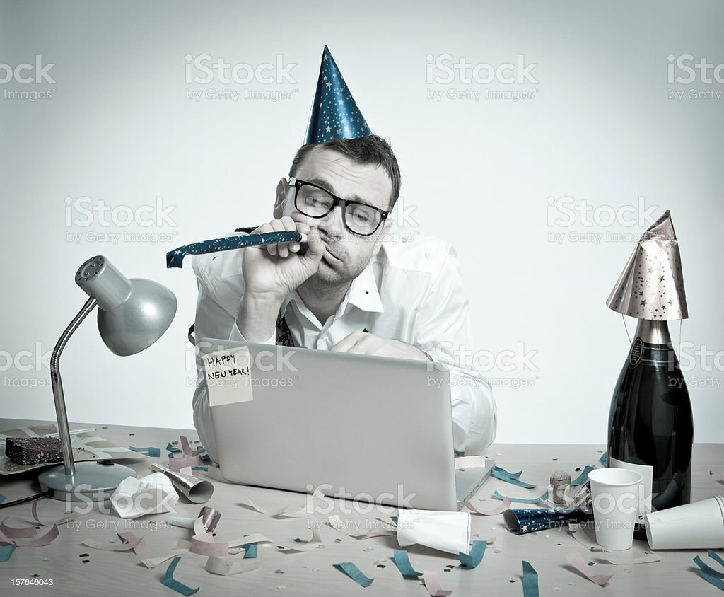 Happy New Year, hungover man behind laptop, office interior, retro royalty-free stock photo