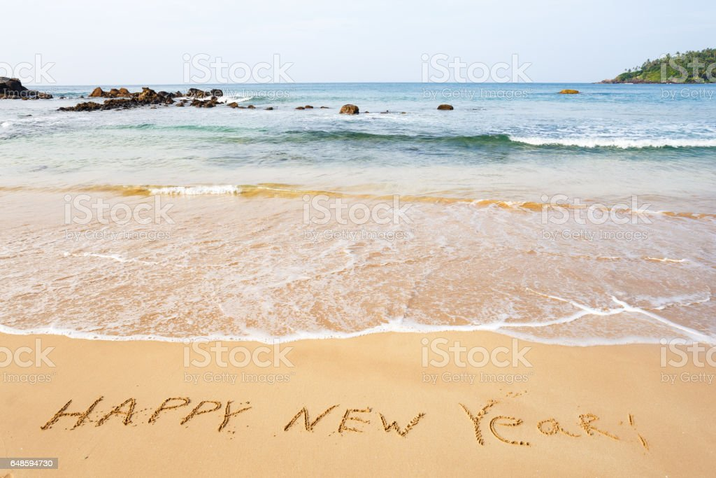 Happy New Year text on the sea beach. stock photo