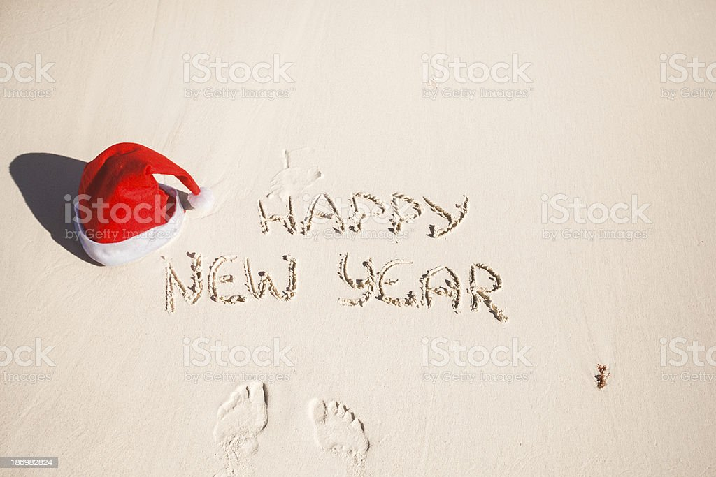 Happy New Year written in the sand and Santa Hat royalty-free stock photo