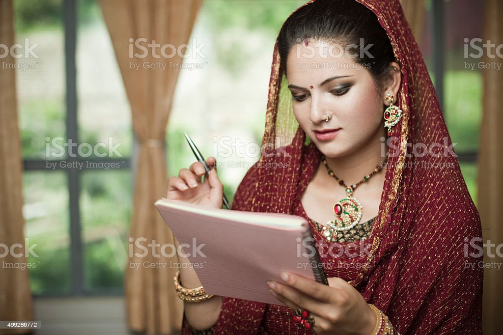 Happy newly married Indian, young woman reading on notepad. stock photo