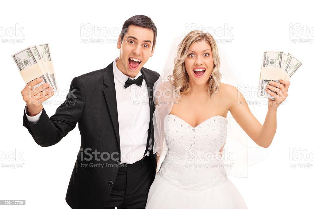 Happy newlywed couple holding money stock photo