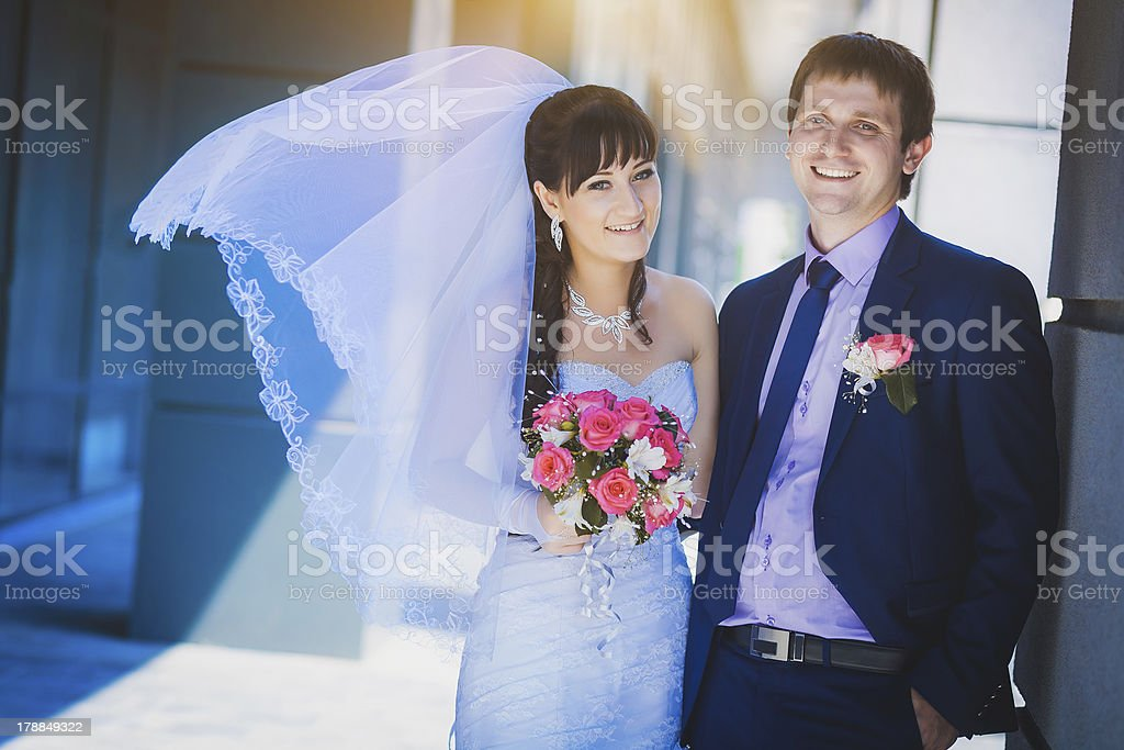 happy newlyweds against a blue modern building stock photo