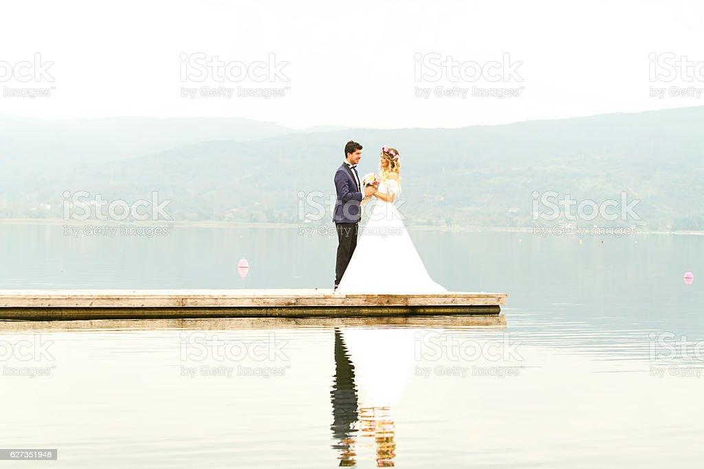 Happy newlyweds standing on pier stock photo