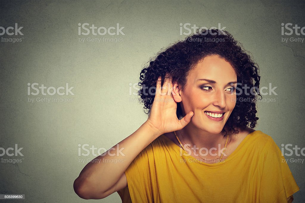 happy nosy woman hand to ear gesture secretly listening stock photo