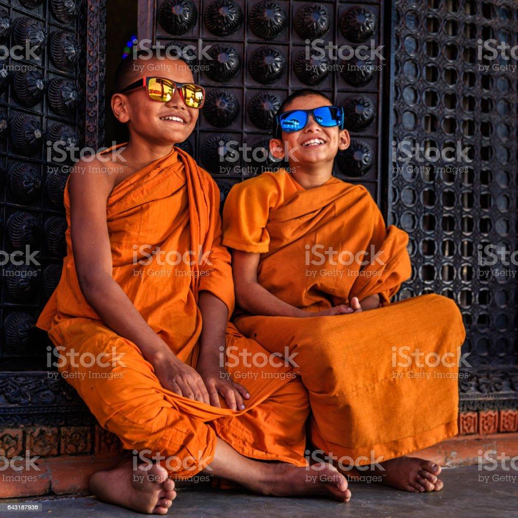 Happy Novice Buddhist monks wearing sunglasses, Bhaktapur stock photo