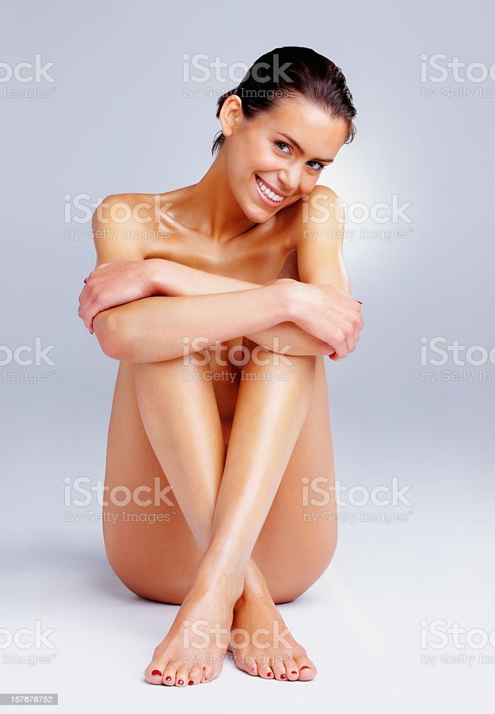 Happy nude woman sitting against colored background royalty-free stock photo