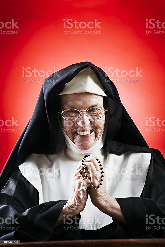 Happy nun smiles as she clasps her rosary royalty-free stock photo