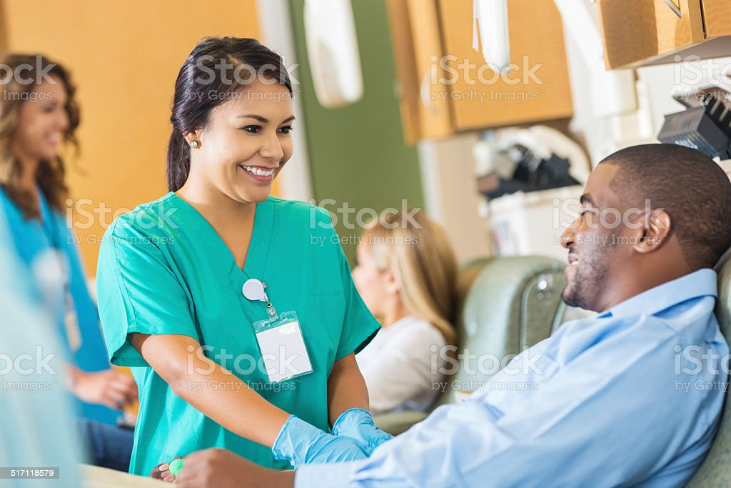 Happy nurse comforting patient while he donates blood to hospital stock photo